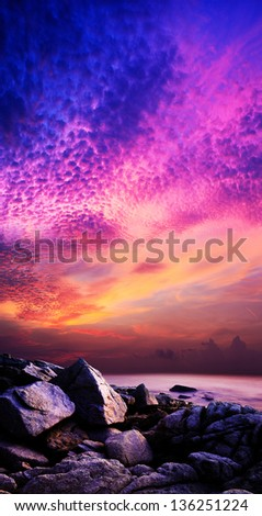 Amazing sunset over the rocky coast. Vertical panoramic composition.
