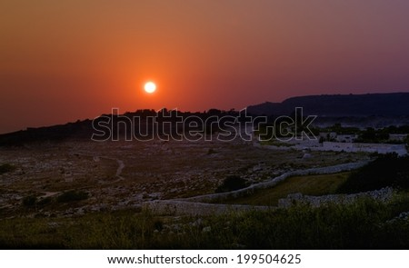 Amazing sunset with pink orange violet red sky and typical maltese farmland in dark light background, postcard, blur, sunset in Malta, Zurieq, Malta  - stock photo