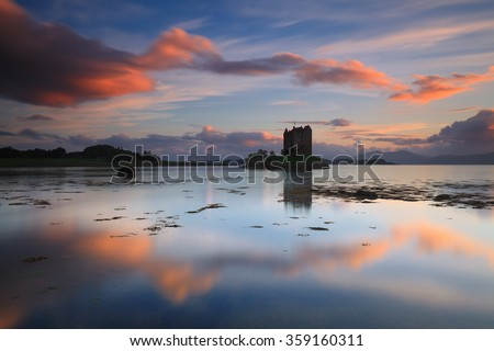 Amazing sunset with reflections at Castle Stalker - stock photo