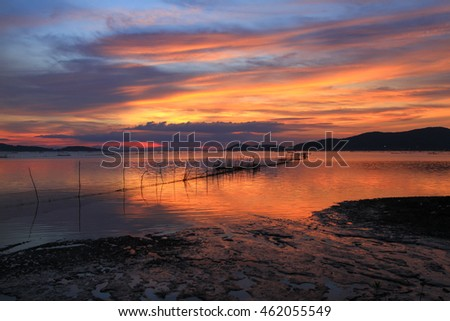 Amazing sunset with silhouette image the net and Lake view as a foreground