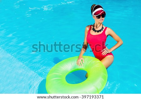 Amazing tan slim woman in stylish red one-piece swimsuit  posing  in pool  with  rubber ring, Outdoor fashion portrait of pretty lady enjoying  summertime  on her vacation.