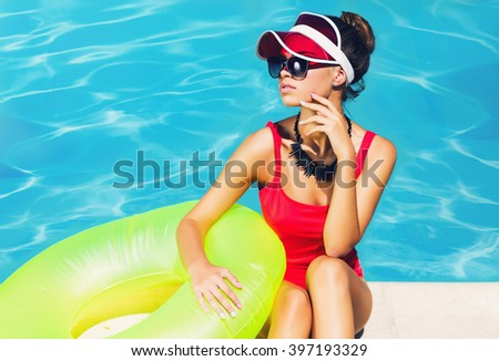 Amazing tan slim woman in stylish red one-piece swimsuit  sitting on steps near pool  with  rubber ring, Outdoor fashion portrait of pretty lady enjoying  summertime  on her vacation. - stock photo