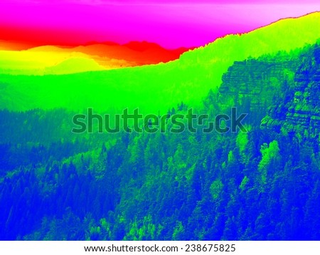 Amazing thermography photo of hilly landscape. Autumn sunset above long deep valley with forest. - stock photo