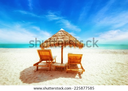 Amazing  tropical beach landscape with thatch umbrella and chairs for relaxation on sand. Travel background and destinations - stock photo
