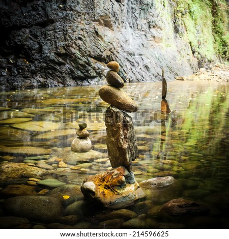 Amazing tropical rain forest landscape with lake and balancing rocks tower for zen meditation practice. Nature background - stock photo