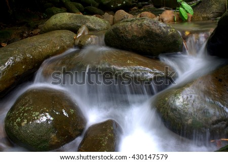 Amazing tropical rain forest landscape with water flow and balancing rocks tower for zen meditation practice. Nature background. long expose image - stock photo