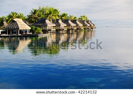 Amazing tropical resort with huts over blue water - stock photo