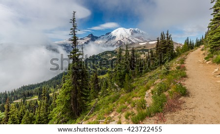 Amazing view at the snowy peaks which rose against the blue of a cloudless sky. Narrow rocky trail high in the mountains. MOUNT FREMONT LOOKOUT TRAIL, Sunrise Area, Mount Rainier