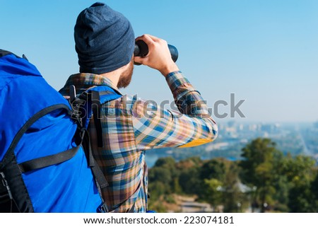 Amazing view. Handsome young bearded man carrying backpack and looking through binoculars at view - stock photo