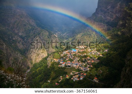 amazing view of a small cozy village Curral das Freiras with a rainbow above, Madeira, Portugal - stock photo