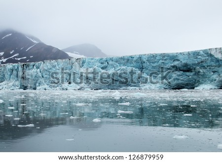 Amazing view of melting blue glacier, calm water and black mountain covered with snow against the background cloudy grey sky with heavy fog in Spitsbergen (Svalbard island), Greenland Sea, Norway - stock photo