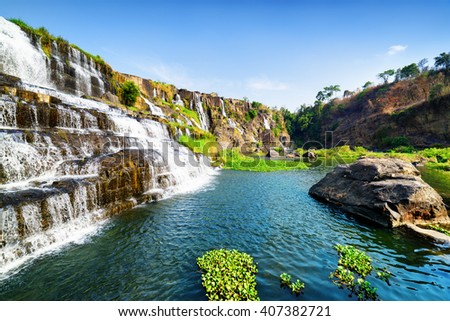 Amazing view of natural cascading waterfall with crystal clear water and scenic pool among rocks in summer. Sunny landscape in Vietnam. The Pongour waterfall is a popular tourist destination of Asia. - stock photo