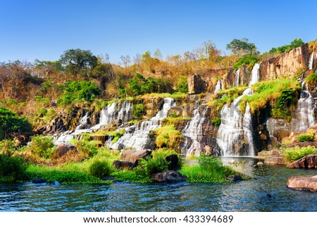Amazing view of natural cascading waterfall with crystal clear water in autumn. Beautiful sunny fall landscape in Vietnam. The Pongour waterfall (PonGour) is a popular tourist destination of Asia. - stock photo