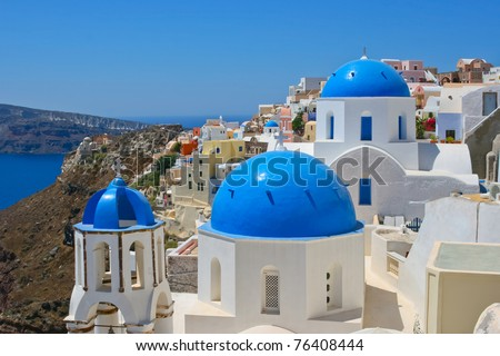 Amazing view of Oia on island of Santorini in Greece. Traditional architecture with famous blue churches. - stock photo