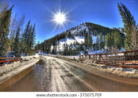 Amazing view of the sun over a snowy bridge road with a mountain landscape in Aspen during the winter. - stock photo