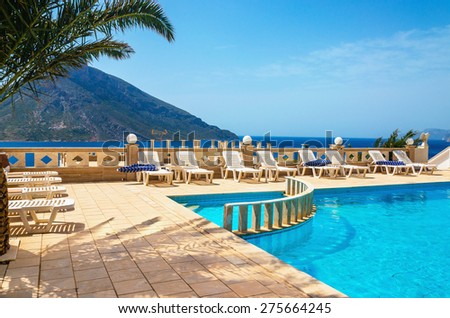 Amazing view on swimming pool area and sunbeds under palm tree with amazing view on coast and sea in background in sunny summer day, Greece - stock photo