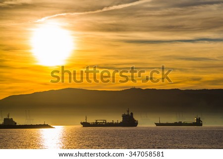 Amazing view on the coastline near Gibraltar during sunset and huge tanker ships around docked near the coastline - stock photo
