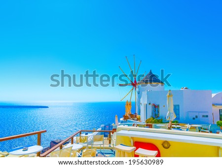 Amazing view to the sea including a pictorial old traditional windmill in Oia the most beautiful village of Santorini island in Greece - stock photo