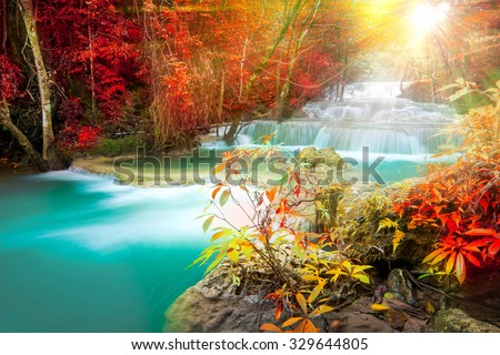 Amazing waterfall in colorful autumn forest with sunlight  - stock photo