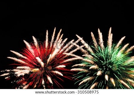 Amazing white-red and white-green fireworks on dark background. Close up - stock photo