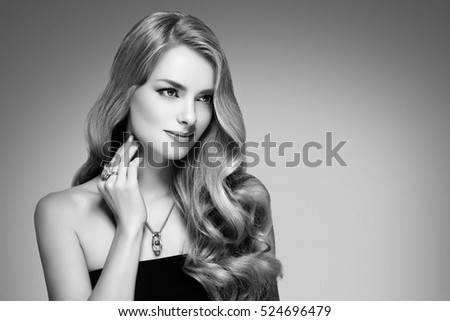 Amazing woman portrait. Beautiful girl with long wavy hair. Blonde model with hairstyle black and white