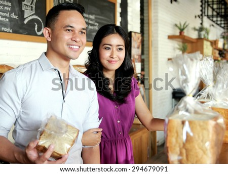 amazing young couple smiling while shopping at bakery shop - stock photo