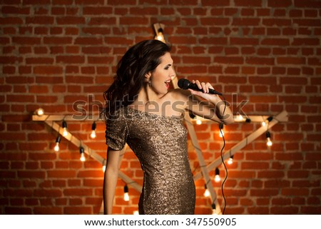 Amazingly beautiful sexy woman singing on stage - stock photo