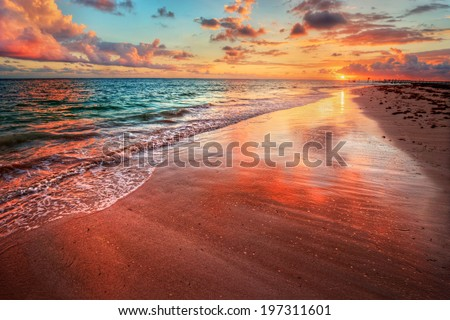 Amazingly colorful sea beach sunset with reflective red sand and bright clouds  - stock photo