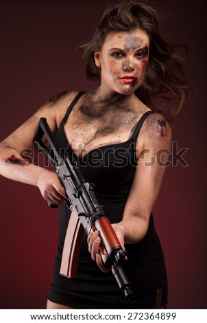 Amazon girl in a black dress holding a gun  - stock photo