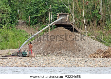 AMAZONIA, PERU - CA NOV 2011 - Local Peruvians participate in illegal gold mining along the Madre de Dios river. This activity has forced the tribes to the riverbank where fatal conflicts arise. - stock photo