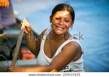 AMAZONIA, PERU - NOV 10, 2010: Unidentified Amazonian woman raws a wooden boat. Indigenous people of Amazonia are protected by COICA (Coordinator of Indigenous Organizations of the Amazon River Basin) - stock photo