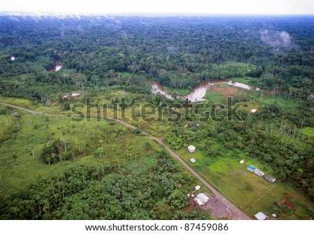 Amazonian rainforest in Ecuador, road foreground bringing colonists who have cut down the forest, but with primary forest beyond the river in the background - stock photo