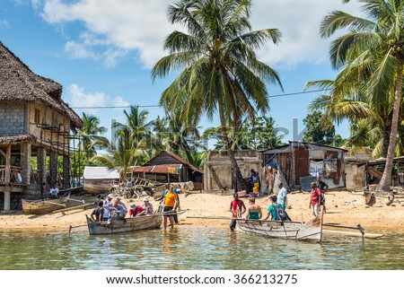 AMBATOZAVAVY, NOSY BE, MADAGASCAR - DECEMBER 19, 2015: Tourists take places on the traditional wood pirogue with outrigger in the Ambatozavavy village on the island of Nosy Be, Madagascar.  - stock photo