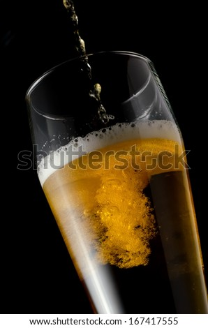 Amber beer flowing in glass on a black background - stock photo