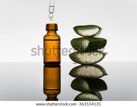 Amber bottle with aloe vera leaf cut into pieces and dropper