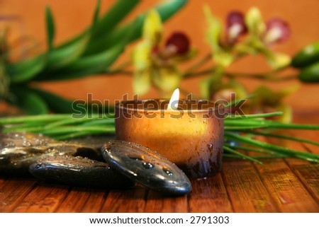 Amber candle and spa stones with orchid  on bamboo - stock photo