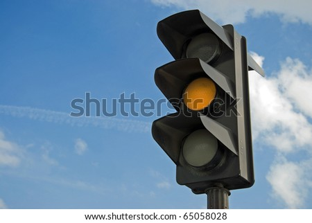 Amber color on the traffic light with a beautiful blue sky in background - stock photo