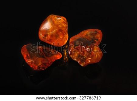 amber gemstone on black. Soft focus, photo toned - stock photo