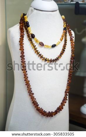 Amber jewelry in a shop window closeup - stock photo