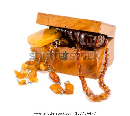 amber stone apparel jewelry in vintage wooden box chest isolated on white. - stock photo