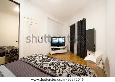 Ambient of a modern sleep room (bedroom) interior with plasma tv - stock photo