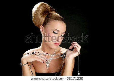 Ambition and greed in fashion woman with jewelry in hands on black background - stock photo