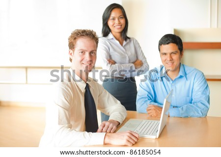 Ambitious British Caucasian businessman sitting, smiling, looking at camera leading business meeting with diverse Asian female and Hispanic male minority team at conference room table. Horizontal