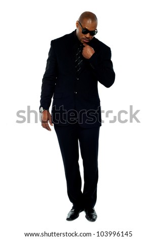 Ambitious corporate man holding microphone placed on his suit and speaking. Full-length shot - stock photo