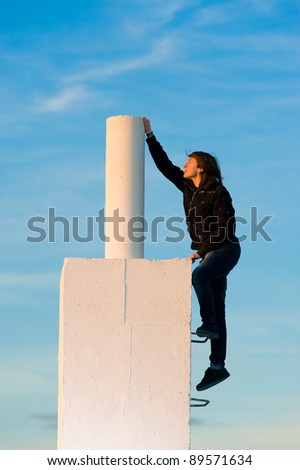 Ambitious teenager about to reach the top, a success concept - stock photo