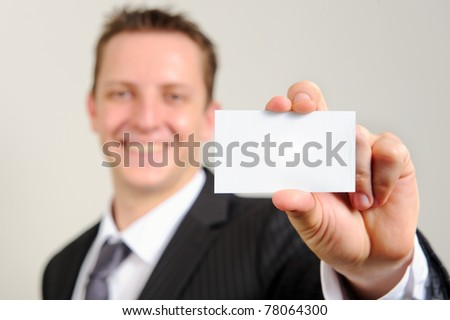 Ambitious white man in business suit smiles confidently and holds out his business card; selective focus on card - stock photo