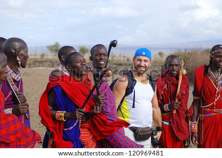 AMBOSELI, KENYA - OCT 13: Group of unidentified African men from Masai tribe dance with a tourist during a traditional show on Oct 13, 2011 in Amboseli, Kenya. They are nomadic and live in villages. - stock photo