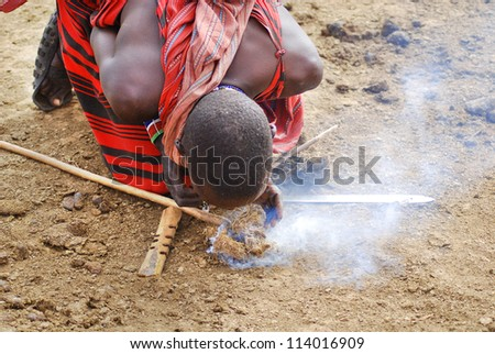 AMBOSELI, KENYA-OCT. 13: Portrait of unidentified young Maasai warriors shows how to make fire in a traditional way to guests visiting their village taken on Oct 13, 2011 in Masai Mara, Kenya. - stock photo