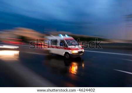 Ambulance car speeding, blurred motion. Deliberately blurred to convey  speed. - stock photo