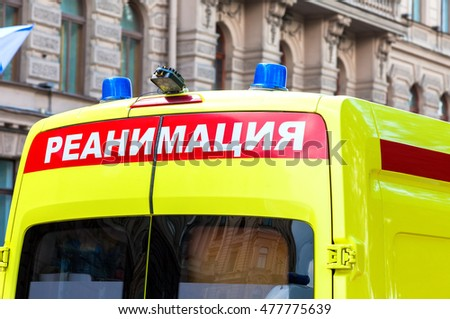"Ambulance car with Blue Flashing Light on the roof. Text in russian: ""Reanimation"""